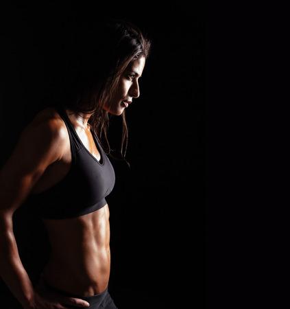 mujer deportista: Imagen de la mujer de la aptitud en ropa deportiva mirando de lejos sobre fondo negro. Hembra joven con cuerpo muscular perfecto. La determinación y confianza.