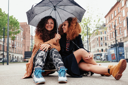 mixed ethnicities: Two female friends sitting together on skateboard. Smiling young women outdoors on city street with umbrella.