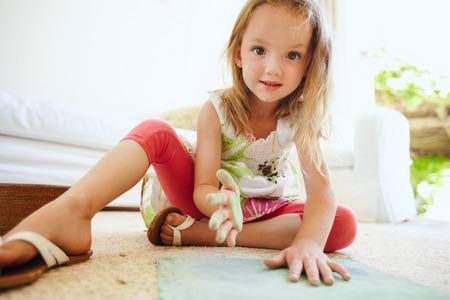 niñas jugando: Retrato de la hermosa pequeña colegiala colorear una imagen. Manos de la muchacha pintado con el color tiza verde mirando a la cámara.