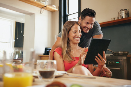 幸せな若いカップル朝は、キッチンでデジタル タブレットを使用します。タッチパッドでの彼女のボーイ フレンドに何かを示す若い女性の笑みを浮