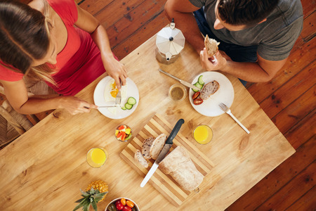 Top view of couple enjoying a healthy morning breakfast in kitchen at home. Breakfast table with loaf of bread, fruits, juice and coffee.