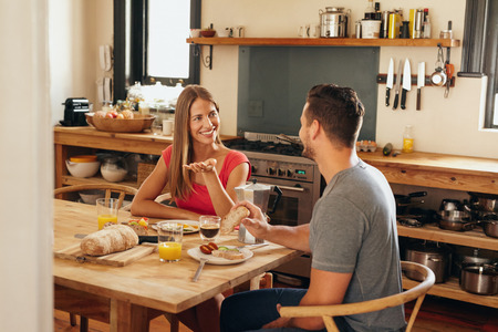 sitting at table: Happy young couple sitting at breakfast table in morning having a conversation. Young woman talking with her boyfriend while eating breakfast together in kitchen. Stock Photo
