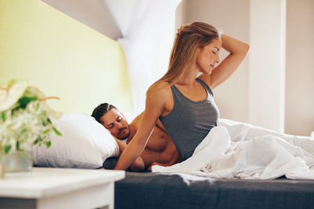 wife and husband: Portrait of attractive young woman waking up in morning with her husband sleeping behind her. Caucasian woman sitting on bed with man sleeping.