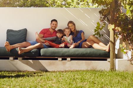 カメラで笑顔のパティオに座って幸せな若い家族の肖像画。彼らの裏庭でソファの上に座って子供たちのカップルします。