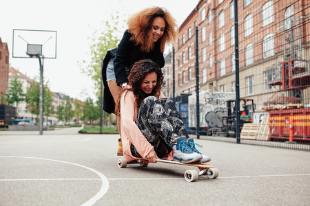 pushed: Playful photo of two women outdoors. Young woman sitting on longboard being pushed by her friend along the road.
