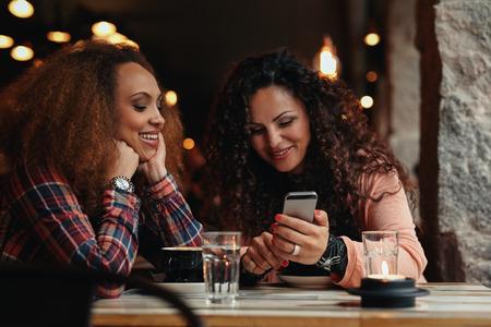 vida social: Dos muchachas que se sientan en una mesa en la cafeter�a. Una mujer que muestra las fotos en su tel�fono m�vil a su amiga.