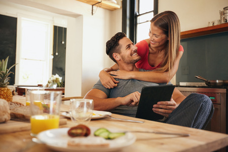 parejas enamoradas: Disparo de la joven pareja amorosa en la cocina por la mesa de desayuno en la mañana. Hombre que usa el digital de la tabla mientras que la mujer lo abrazó por detrás, ambos mirando el uno al otro sonriendo.