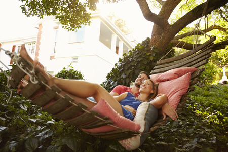 people relaxing: Portrait of an affectionate young couple lying on a hammock looking away smiling. Romantic young man and woman on garden hammock in backyard. Stock Photo