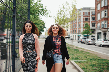 city scene: Outdoor shot of two girlfriends walking through town. Happy young women walking together along a city street.