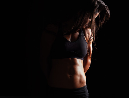 sports: Portrait of sensual young woman wearing sports bra looking down while standing on black background. Female model with muscular body.