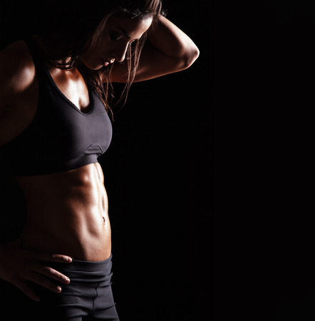 Slim and fit woman belly with hands on hips. Mid section of young woman body with muscular abs on black background with copyspace.