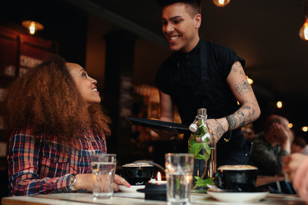 serving food: Woman talking to waiter at restaurant. Young woman sitting at cafe with waiter standing by smiling. Stock Photo