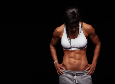 muscle: Imagen de la mujer joven en ropa deportiva mirando hacia abajo contra el fondo negro con copyspace. Femenina muscular acumulación después del entrenamiento. Foto de archivo