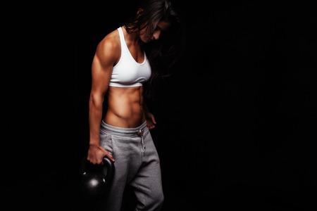 Mujer que sostiene joven campana hervidor ajuste que ejercita contra el fondo negro. Muscular mujer haciendo ejercicio de crossfit.