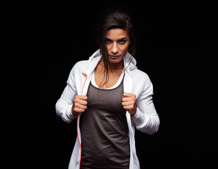 Young woman looking at camera with an attitude. Fitness female model in sportswear on black background