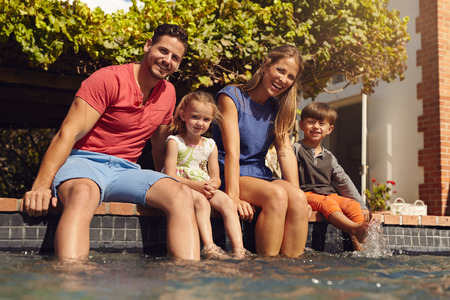 parent child: Family sitting with feet in swimming pool. Young family of four sitting on edge of their pool looking at camera on a sunny day.