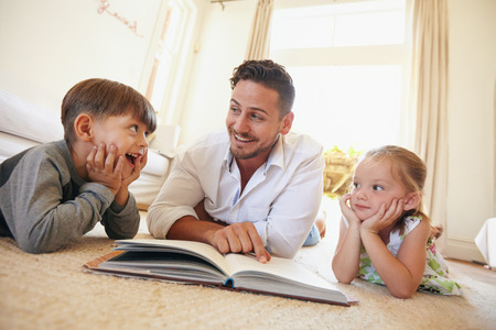 Shot of happy young family lying on the floor reading a book. Young man reading stories to his little son and daughter at home. Stock Photo