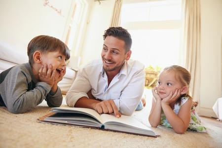 Shot van gelukkig jong gezin liggend op de vloer het lezen van een boek. Jonge man het lezen van verhalen aan zijn kleine zoon en dochter thuis.