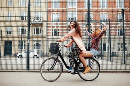 ciclismo: Retrato de dos mujeres jóvenes felices disfrutando de paseo en bicicleta en calle de la ciudad. Amigos femeninos que montan en una bicicleta.