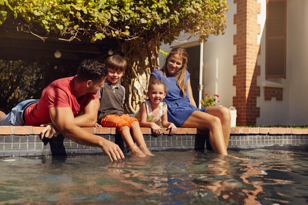 two generation family: Portrait of young family with two children relaxing by their swimming pool having fun. Parents with kids sitting on the edge of pool on a sunny day.