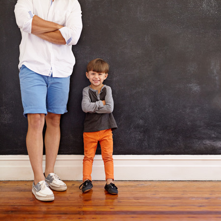 summer wear: Indoor shot of little boy standing next to his father with hands folded and smiling.  Cropped shot of young man in summer wear with son standing by against black wall at home.