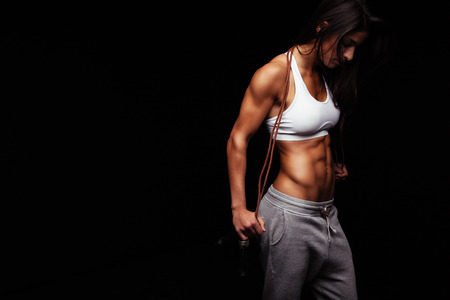 mujeres fitness: Imagen de culturista femenina que sostiene la cuerda que salta mirando hacia abajo. Mujer joven de la aptitud con cuerpo musculoso que presenta en fondo negro Foto de archivo