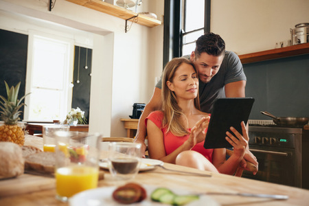 Young couple in kitchen looking at tablet pc. Man standing by his girlfriend sitting using digital tablet in morning. Standard-Bild