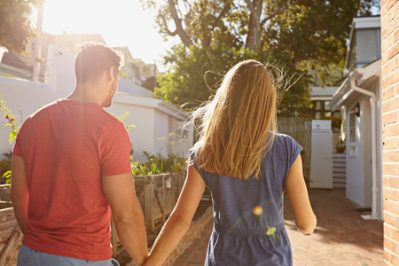 persona caminando: Vista trasera de la joven pareja caminando a su casa juntos. Pareja en el patio trasero de tomar paseo en un d�a soleado.