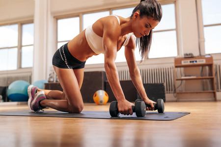 krachtige vrouw: Krachtige vrouw doet push-ups op halters in sportschool. Gespierde vrouwelijke uitoefenen in de health club. Stockfoto