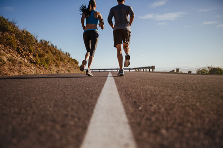 Rear view of two young people training together on road. Man and woman on morning run on summer day. Low angle shot of couple jogging outdoors.