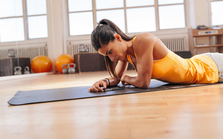 Fitness woman lying on exercise mat looking at her mobile phone. Woman using smart phone after her workout session at gym.