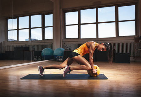 Muscular woman in gym working out on her core body. Strong woman exercising with kettlebell in sports club.