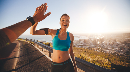 Fit young woman high fiving her boyfriend after a run. POV shot of runners on country road looking happy outdoors with bright sunlight.