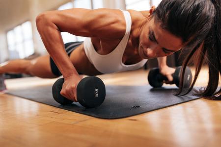muskeltraining: Starke junge Frau macht Push-ups Übung mit Hanteln. Fitness-Modell tut intensives Training in der Turnhalle.