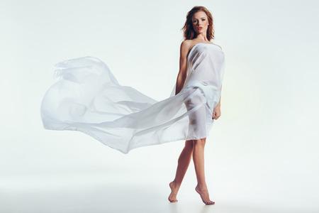 nudo integrale: Sexy donna bruna nuda coperta in tessuto trasparente su sfondo bianco. Bella modello femminile guardando la fotocamera.