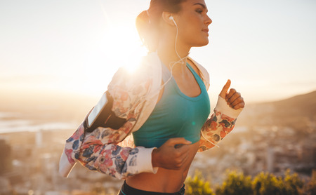 Close-up shot of fitness woman running outdoors. Caucasian female jogging in morning with bright sunlight. Foto de archivo