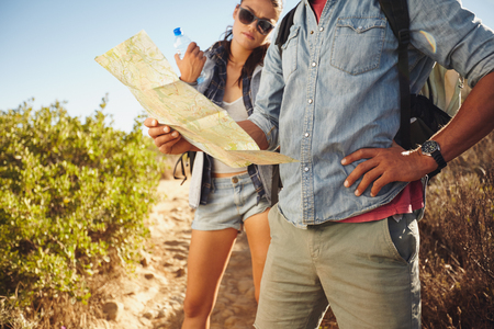 outdoor pursuit: Hiker couple on country walk. Man with map and with woman standing my holding water bottle. Couple stopping to check their map while hiking in countryside. Stock Photo