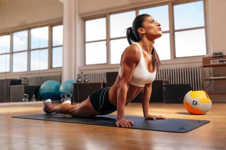 espina dorsal: Mujer haciendo tramo central en la estera de fitness. Mujer joven muscular haciendo ejercicios de estiramiento en el gimnasio.
