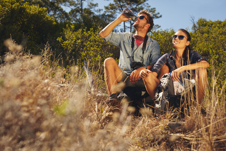 caucasian: Outdoor shot of young couple sitting together taking a break on hike. Caucasian man and woman drinking water while out hiking.