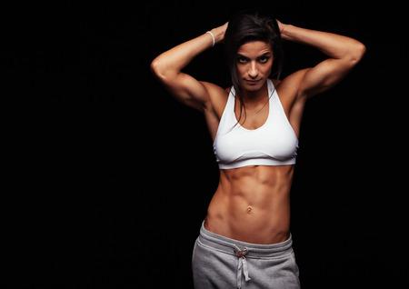 Gespierde vrouw het dragen van fitness kleding poseren tegen een zwarte achtergrond. Kaukasische vrouwelijke model met perfecte abs.
