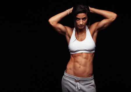 Muscular woman wearing fitness clothing posing against black background. Caucasian female model with perfect abs.