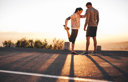 woman stretching: Outdoor shot of fit young joggers stretching before a run together in morning. Young man standing and woman stretching her legs at sunrise.