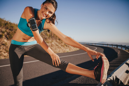 Female athlete stretching her legs outdoor before running. Fit young woman warming up for a run on country road.