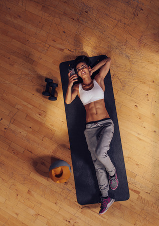 taking a break: Top view of woman relaxing on yoga mat using mobile phone. Fitness female taking a break lying on exercise mat at gym reading text message on her smart phone.