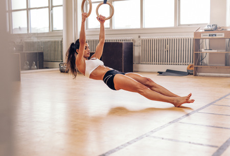 hang body: Young fit woman pulling up on gymnastic rings. Muscular woman exercising on gym.