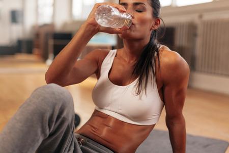 muscular: Fitness mujer bebiendo agua de botella. Muscular joven mujer en el gimnasio tomando un descanso del entrenamiento. Foto de archivo