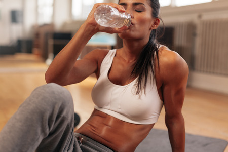 vrouwen: Fitness vrouw drinkwater uit de fles. Gespierde jonge vrouw op sportschool nemen een pauze van de training.