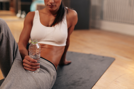 hand holding bottle: Cropped shot of relaxed young woman holding water bottle. Fitness woman in sports wear sitting on exercise mat at gym.
