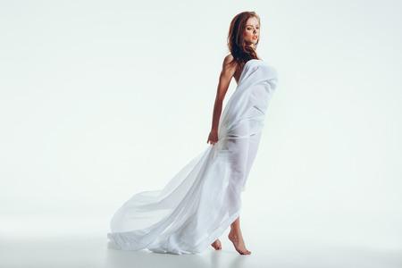 Aantrekkelijke naakt vrouw met een witte stof op haar lichaam poseren op een witte achtergrond. Kaukasische vrouwelijke model staan verpakt in doorzichtige sjaal.