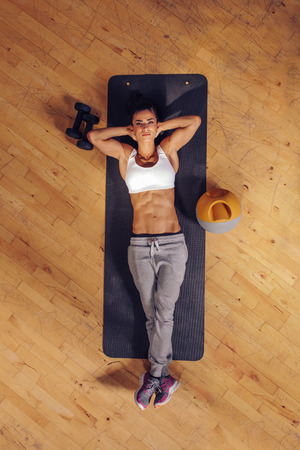 Top view of woman relaxing on yoga mat. Fitness female lying on exercise mat with her hands behind head and looking at camera at gym.